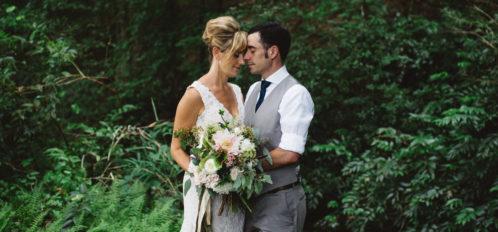 bride and groom posing in greenery