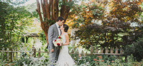 groom kissing bride's forehead in garden