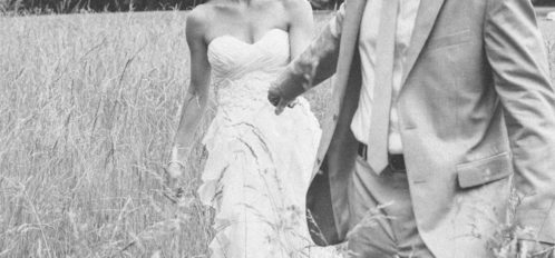 grayscale of bride and groom walking through field together