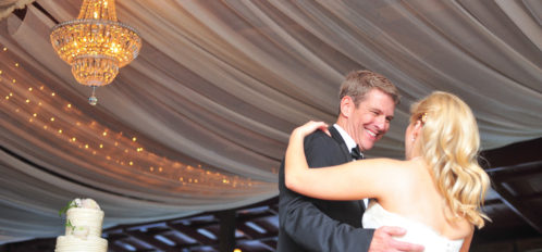 groom smiling down at bride while dancing
