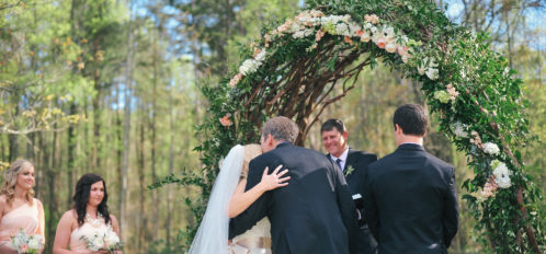 father kissing bride as he gives her away at altar