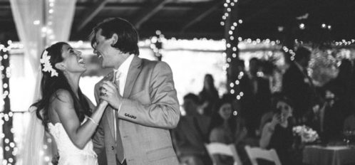 bride and groom dancing and smiling in grayscale