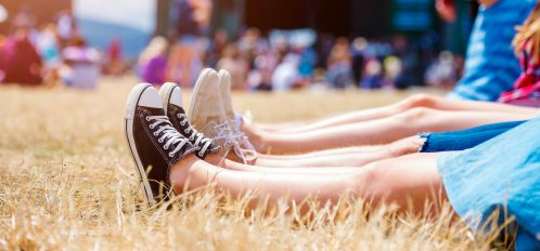 Legs of people at a summer music festival, canvas shoes, sitting on the grass in front of stage