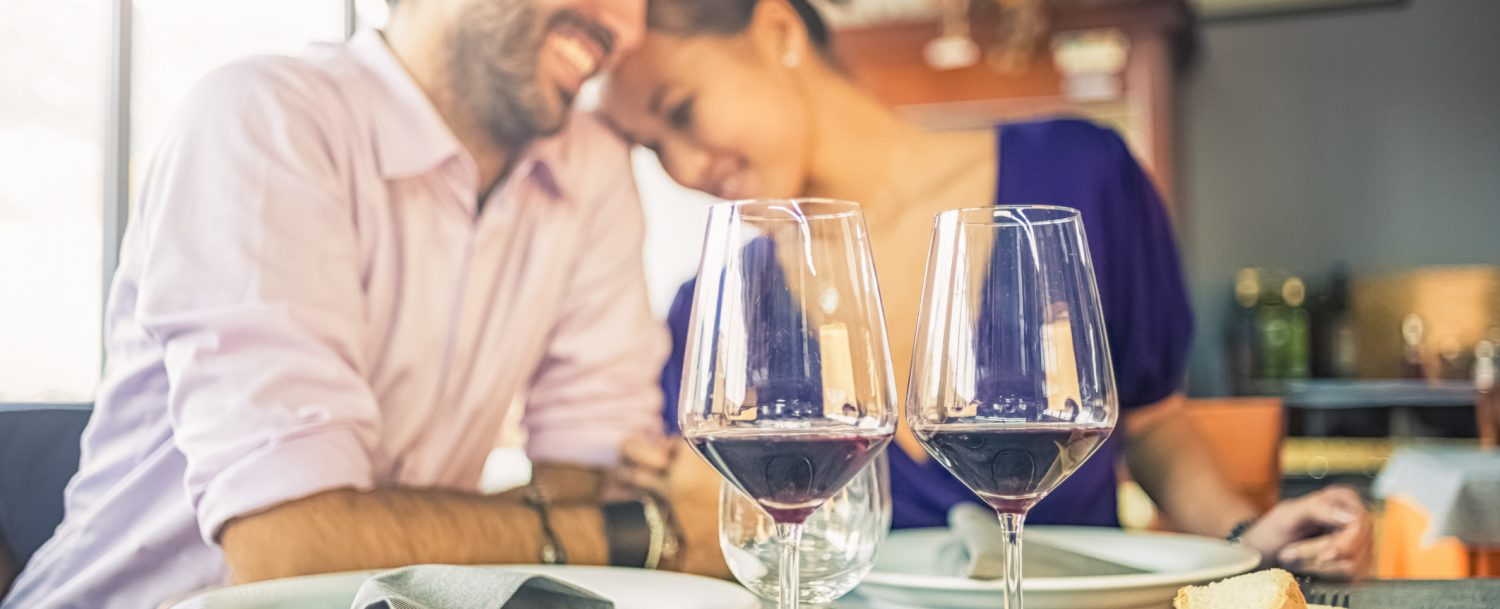 couple cuddling at restaurant with wine