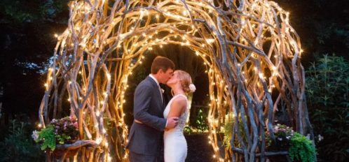 bride and groom kissing under lit archway