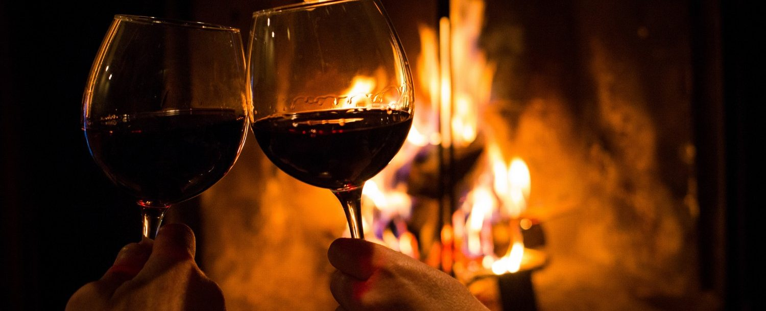 Couple toasting their glasses of wine in front of the fireplace; Winter Getaways in Georgia