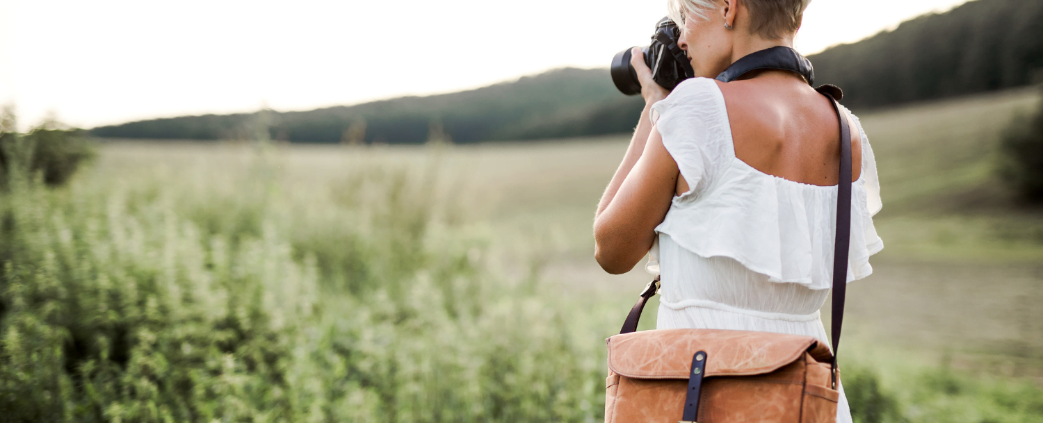 Woman taking photos of Instagrammable spots in a field surrounded by mountains